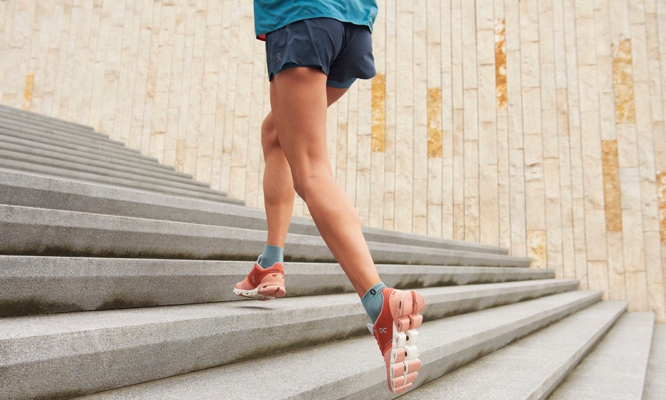 Person running up steps wearing On Running trainers