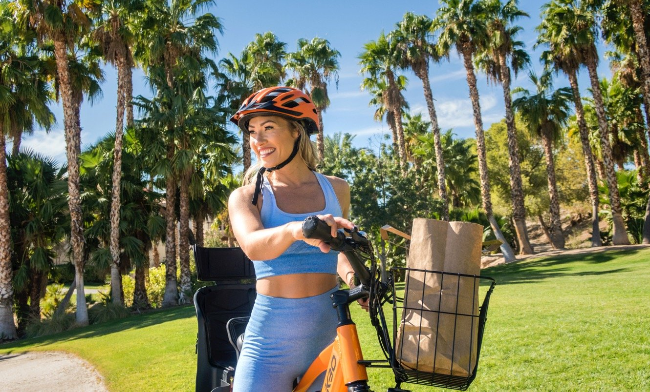 Woman on an e-bike surrounded by palm trees