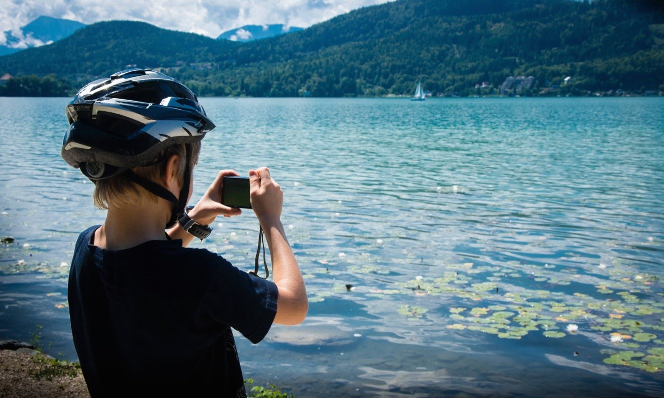 Boy wearing cycling helmet and taking a photograph