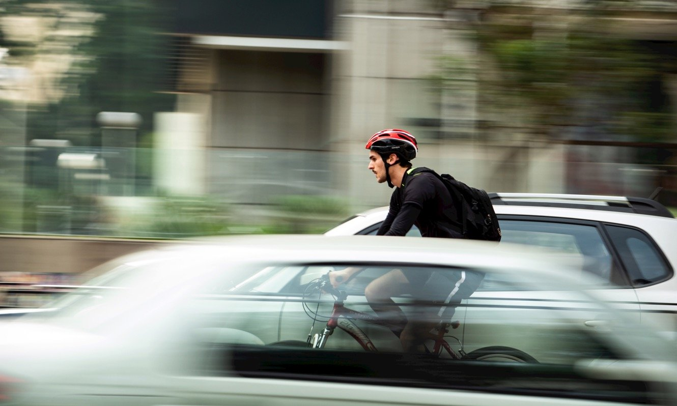 Man cycling through traffic