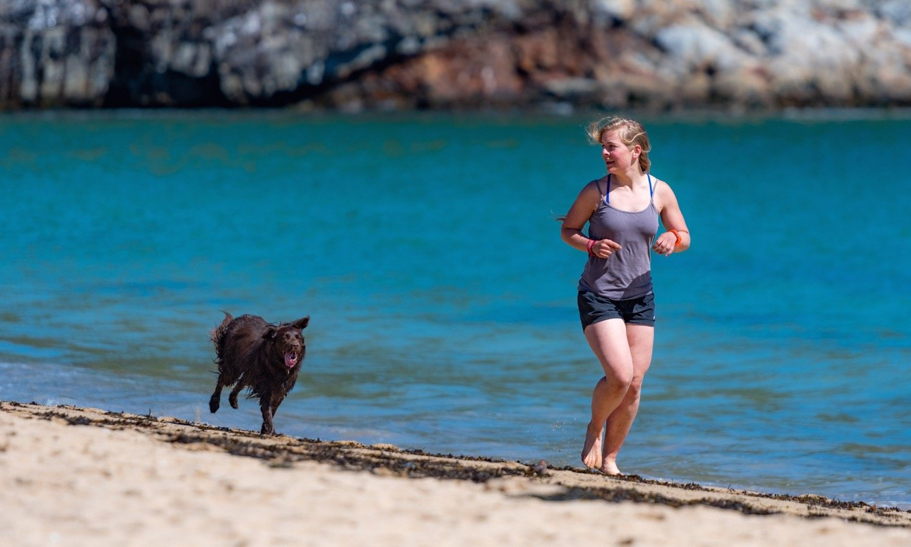 Woman running on the beach with her dog