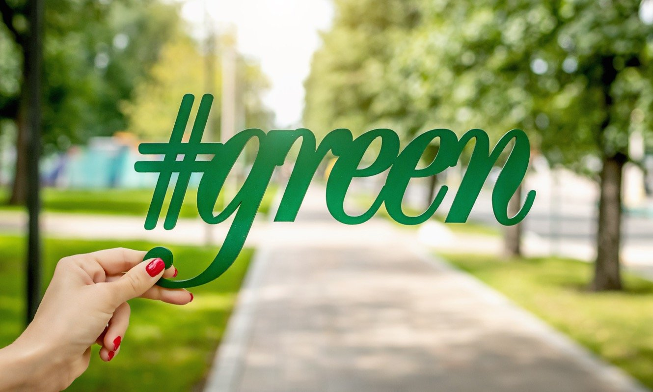 Woman's hand holding a green sign