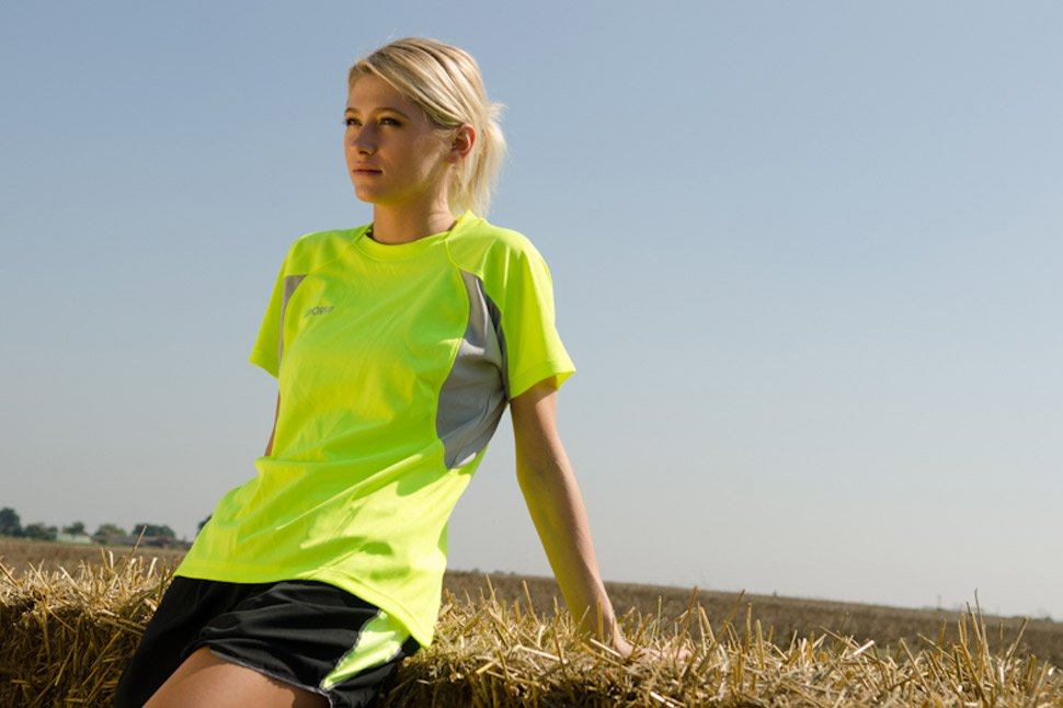 Model wears the classic womens short sleeve top in luminescent high-vis yellow while sitting in the summer sun during a jog