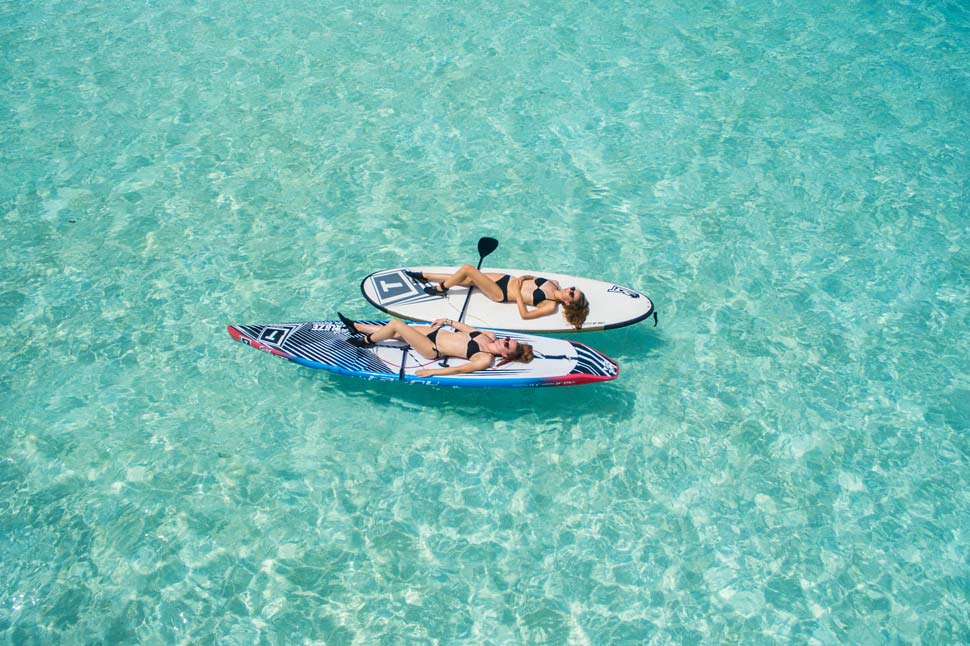 Two women on holiday paddleboarding - a great form of exercise. Photo credit Ishan via Unsplash