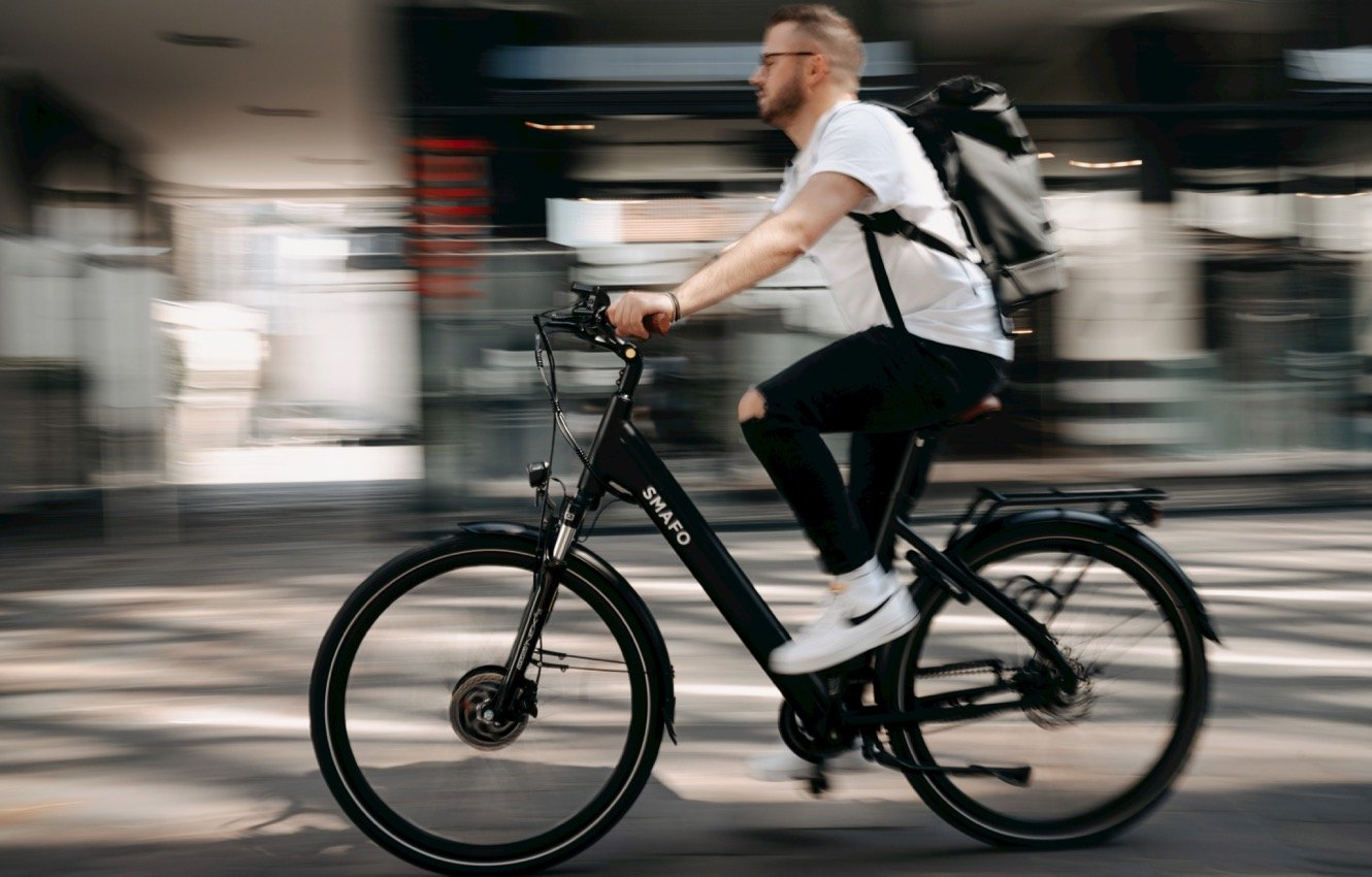 Man riding e-bike through town